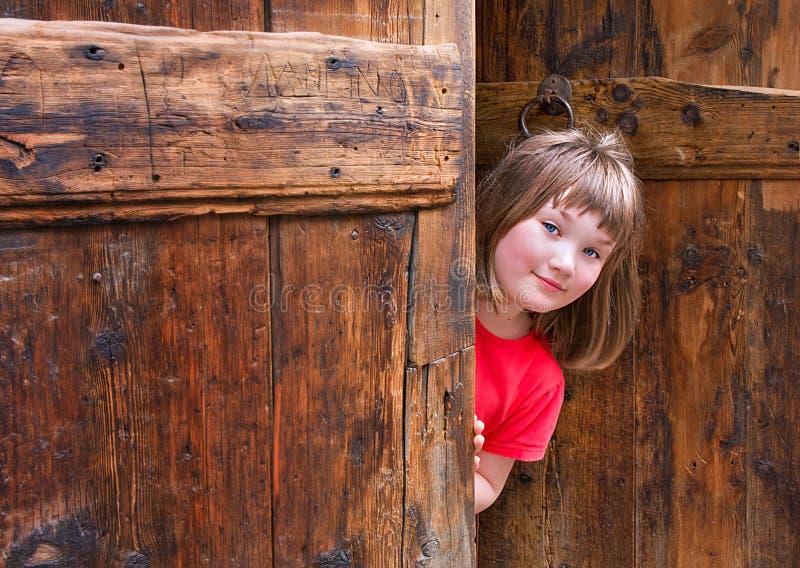 Cute girl peeping behind an old wooden door. Cute girl dressed in red peeping behind an old wooden door royalty free stock photos