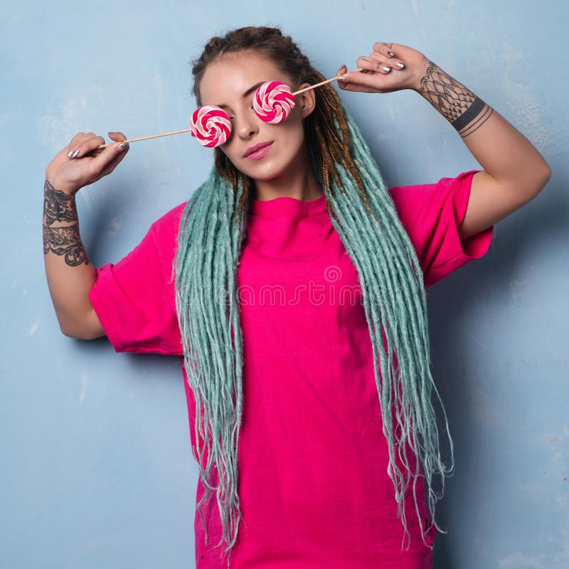 Cute girl in pink t-shirt with dreadlocks and tattoo closes her eyes with lollipops stock image