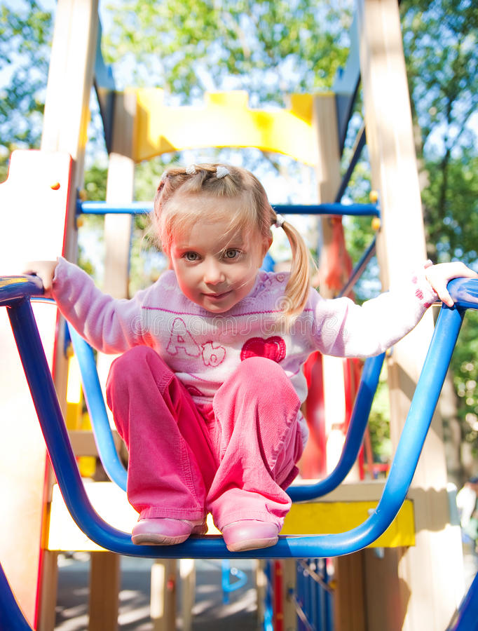 Cute girl on playground equipment. Cute little girl on outdoor playground equipment royalty free stock photography