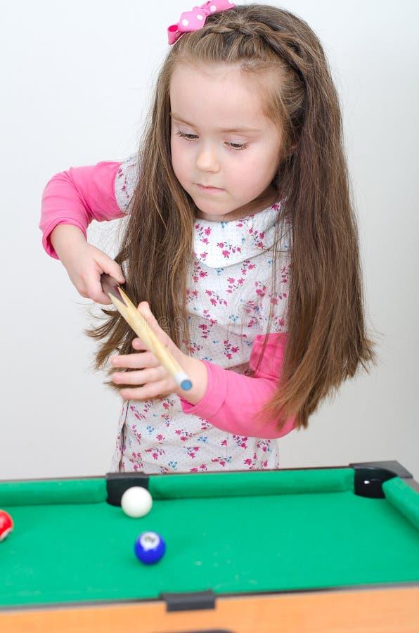 Cute girl playing billiard stock photo