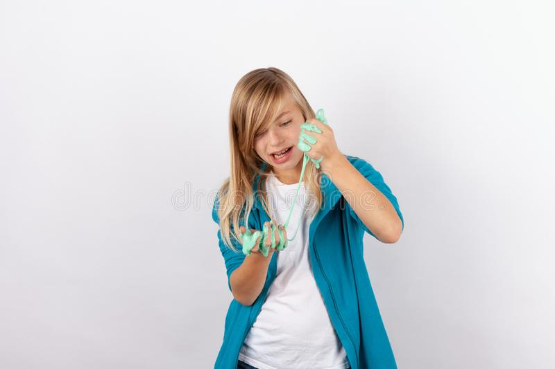 Cute girl playing with green slime royalty free stock photography