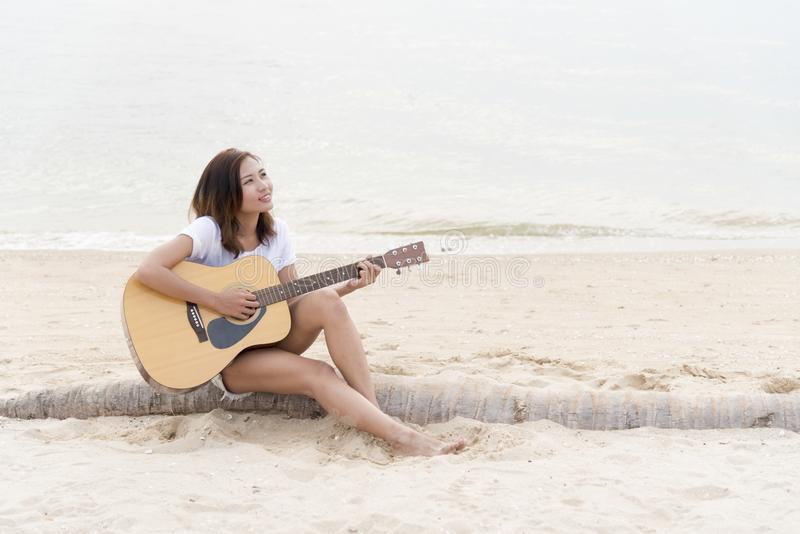 Cute girl playing guitar on the beach. Travel Concept stock photography