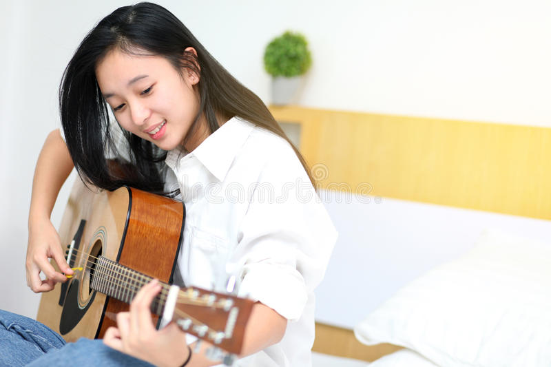 Cute girl playing guitar on the bedroom. royalty free stock images