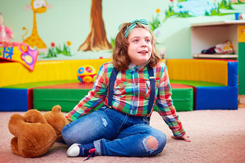 Cute girl playing in kindergarten for kids with special needs stock photos