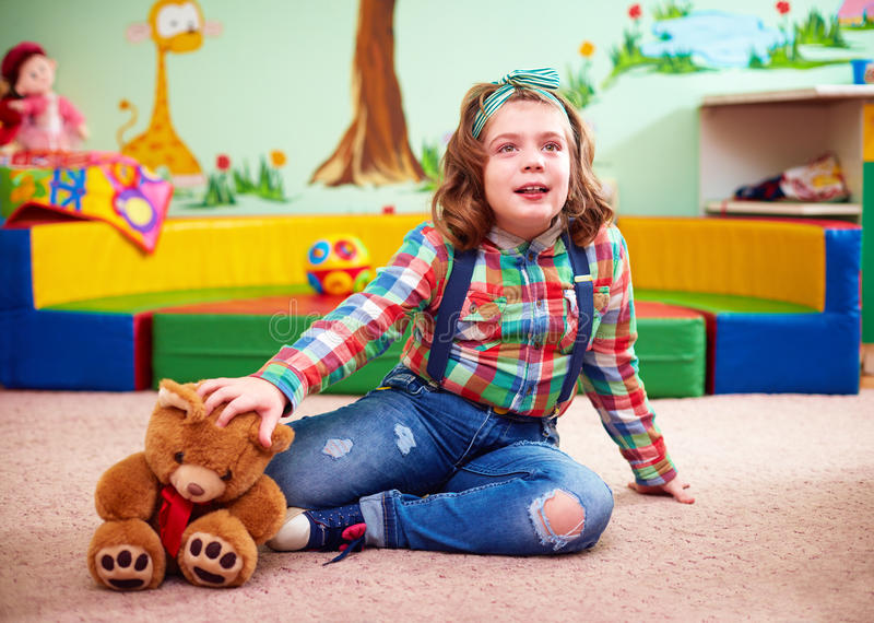 Cute girl playing in kindergarten for kids with special needs royalty free stock images