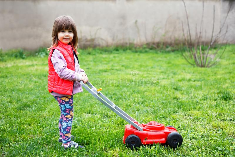Cute girl playing with a lawn mower in the yard stock photo