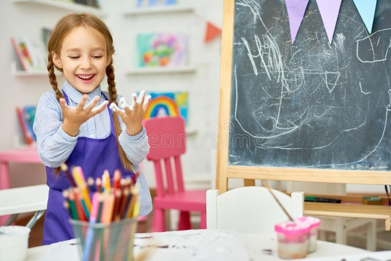 Cute Girl Playing with Paint in Art Class. Portrait of cute little girl enjoying art and craft lesson in development school and smiling happily looking at hands royalty free stock image