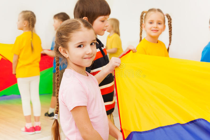 Cute girl playing rainbow parachute with friends royalty free stock images