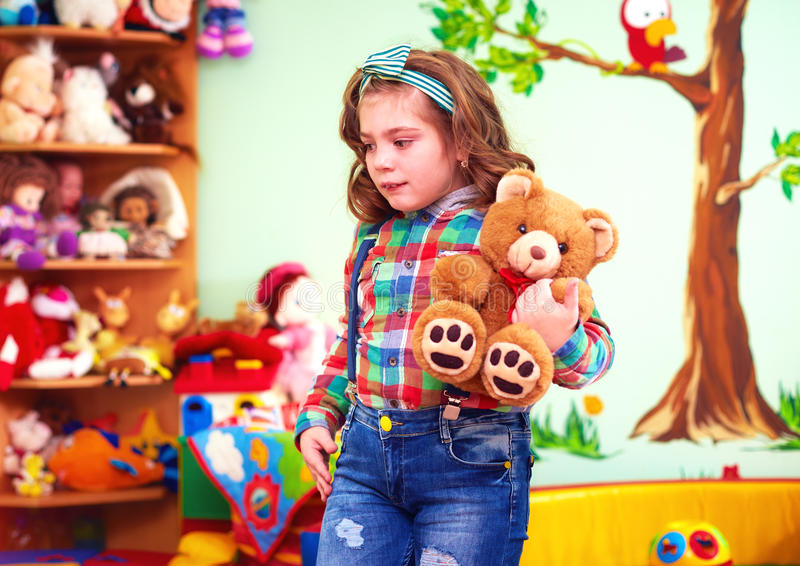 Cute girl playing with toys in kindergarten for kids with special needs stock photo