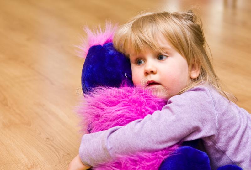 Cute girl with plush toy lying on the floor. stock photo