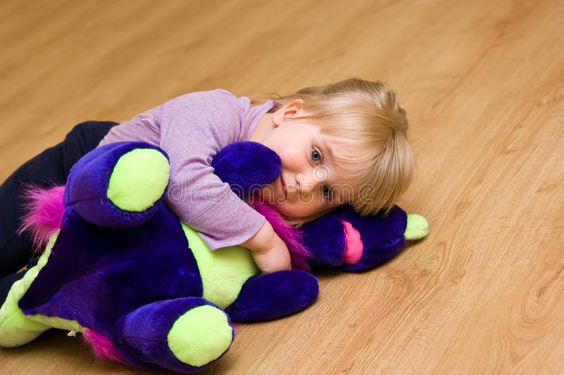 Cute girl with plush toy lying on the floor. stock images