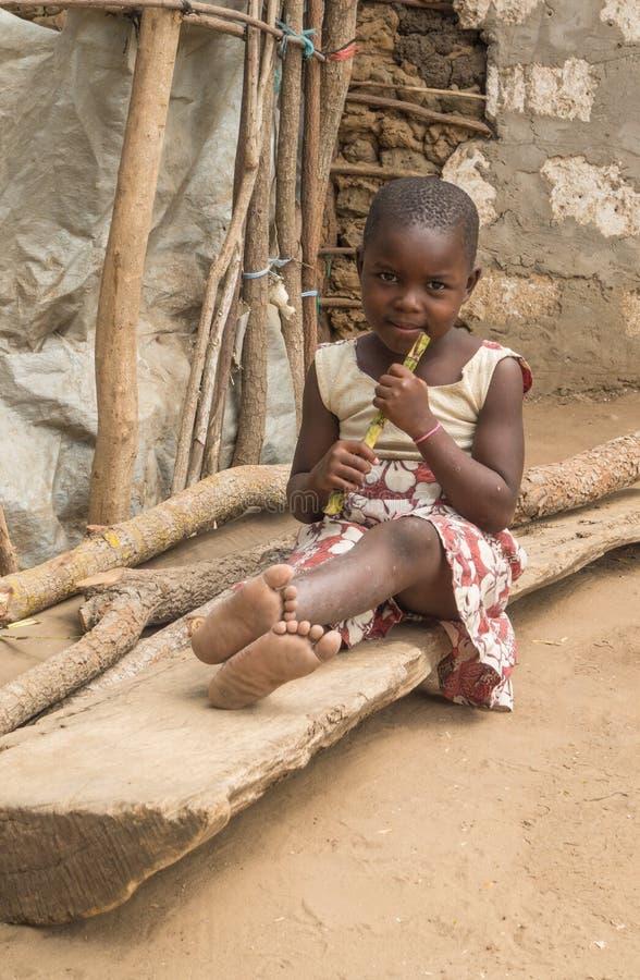 Pokomo girl sitting on log in Kenya, Africa royalty free stock image