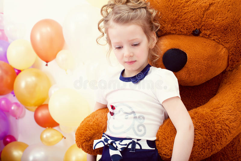 Cute girl posing in embrace with big teddy bear. Image of cute girl posing in embrace with big teddy bear royalty free stock photography