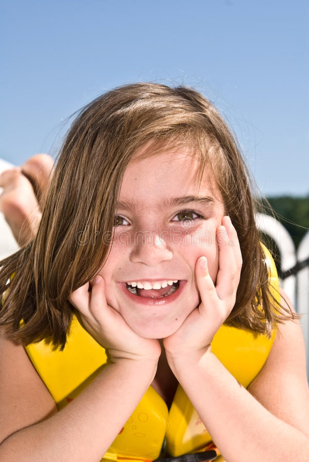 Cute Girl Posing / Outside. A very happy young girl lying in a boat posing with a life jacket on. 6 years old stock photo