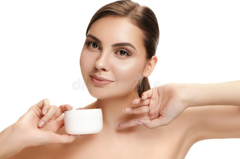 Cute girl preparing to start her day. She is applying moisturizer cream on face. royalty free stock images