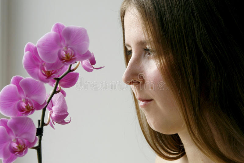 Cute Girl With A Purple Orchid Stock Photos