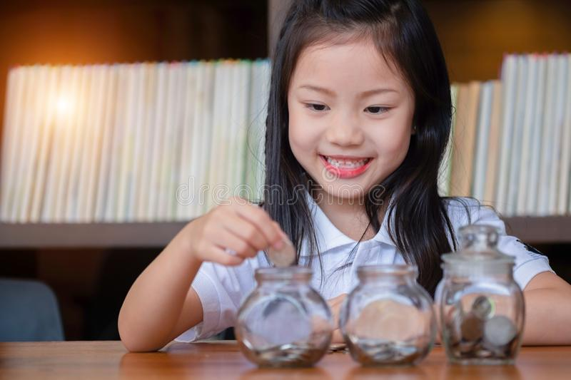 Cute girl putting money coins in glass,saving money concept stock images