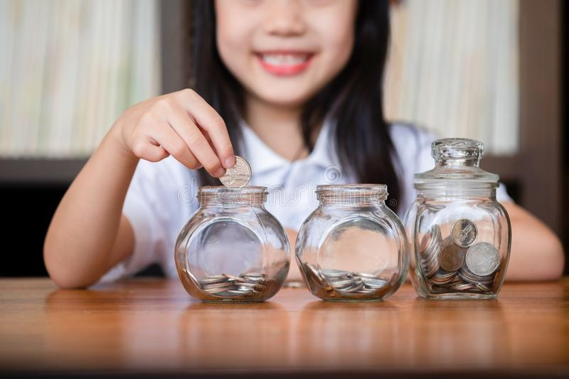 Cute girl putting money coins in glass,saving money concept royalty free stock image