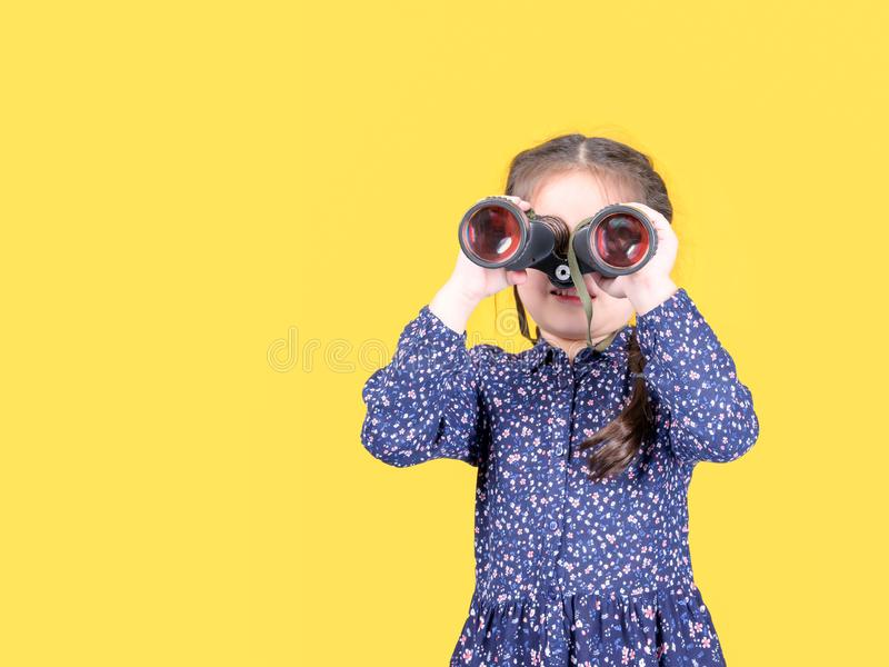 A cute girl raises a binoculars to look at the outside world through the lens royalty free stock photo