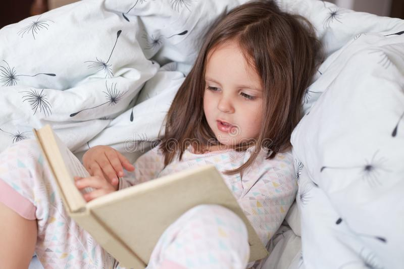 Cute girl reading her favorite fairy tale, child sitting in bed with book, Kid preparing to go to bed, spending pleasant time in. Cozy bedroom. Girl kid with stock photos