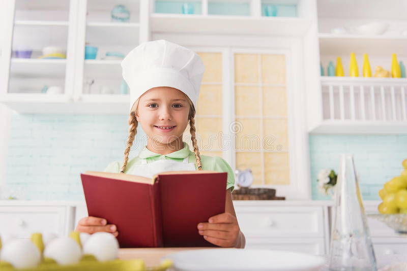 Cute girl reading recipe for cooking royalty free stock photo