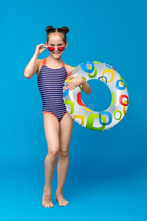 Cute girl ready for swimming, wearing swimsuit and holding inflatable ring stock photo