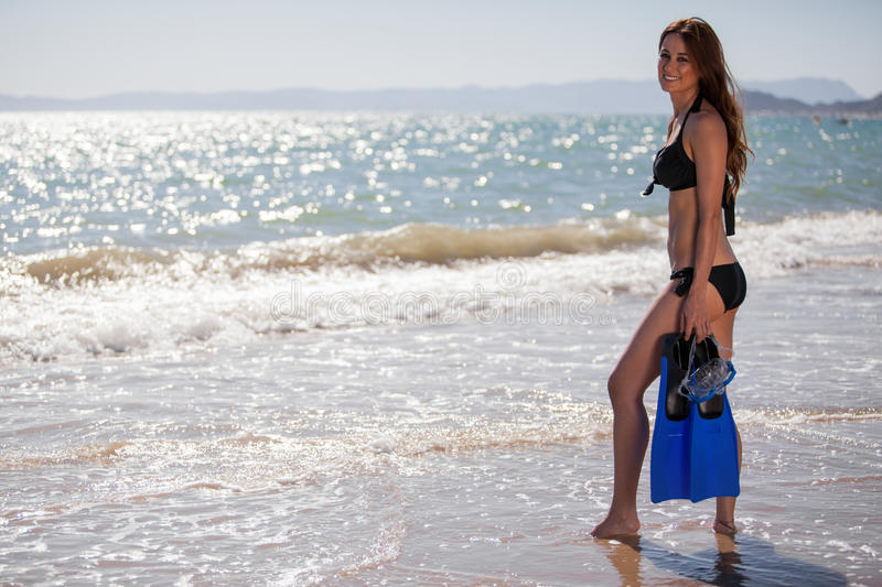 Cute girl ready to dive in the sea. Beautiful young woman holding a pair of flippers before diving in the ocean royalty free stock photo