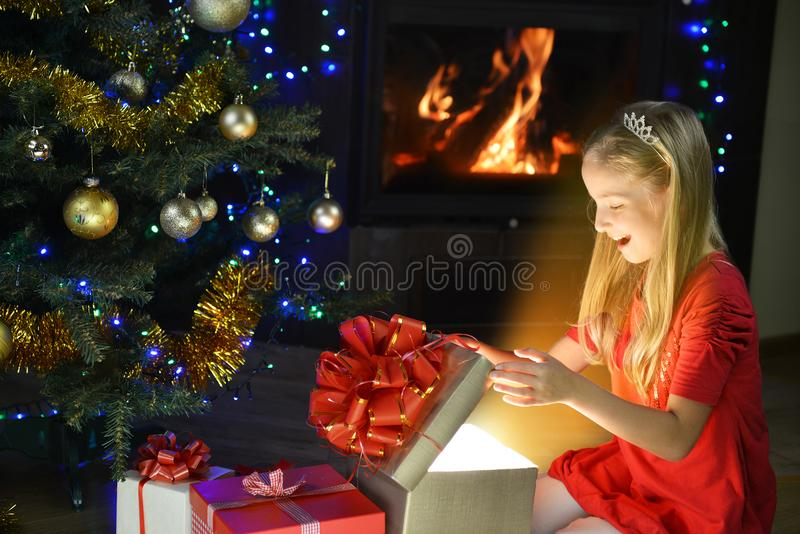 Cute girl. In red dress near Christmas tree stock photo