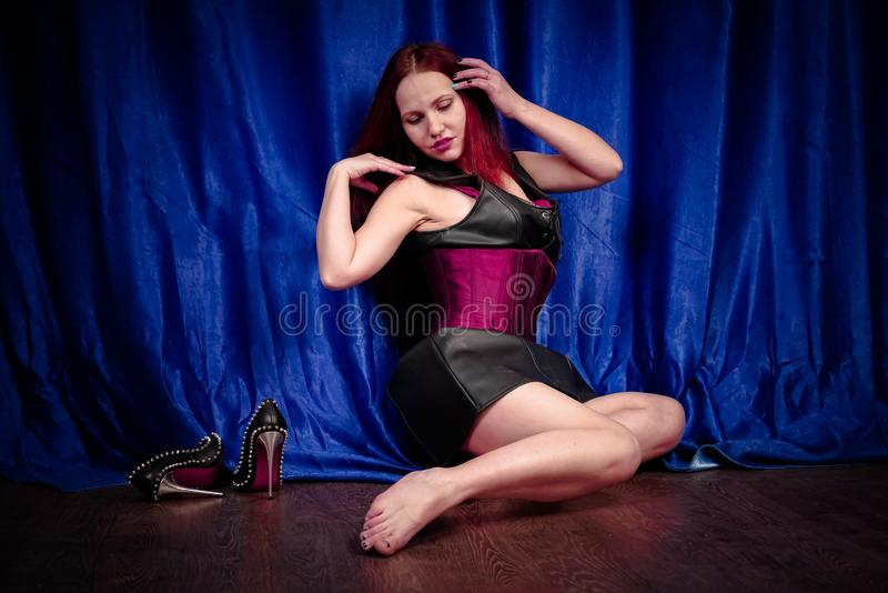 Cute girl with red hair in a leather dress and corset sits on the floor barefoot and enjoys beautiful black shoes with spikes. Beauty stock photos