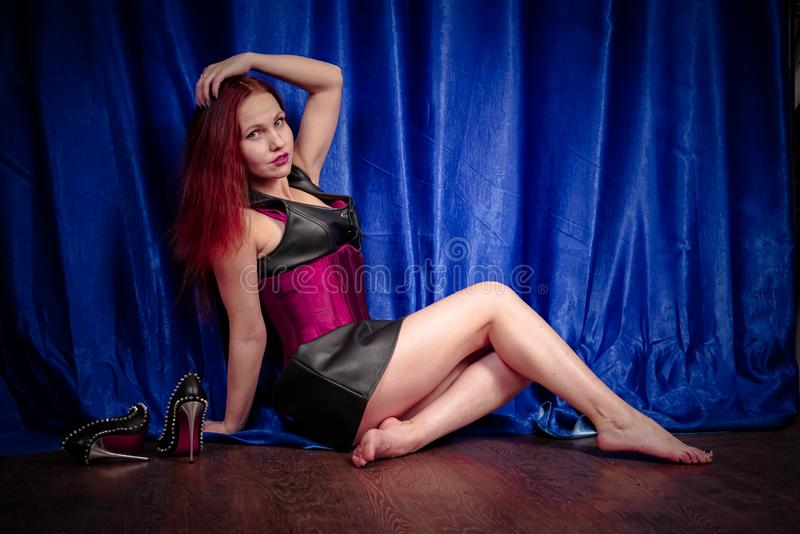 Cute girl with red hair in a leather dress and corset sits on the floor barefoot and enjoys beautiful black shoes with spikes stock photo