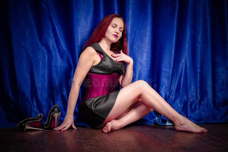 Cute girl with red hair in a leather dress and corset sits on the floor barefoot and enjoys beautiful black shoes with spikes royalty free stock photography