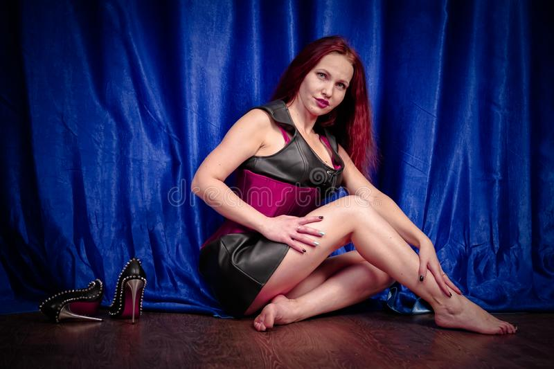 Cute girl with red hair in a leather dress and corset sits on the floor barefoot and enjoys beautiful black shoes with spikes. Beauty royalty free stock images