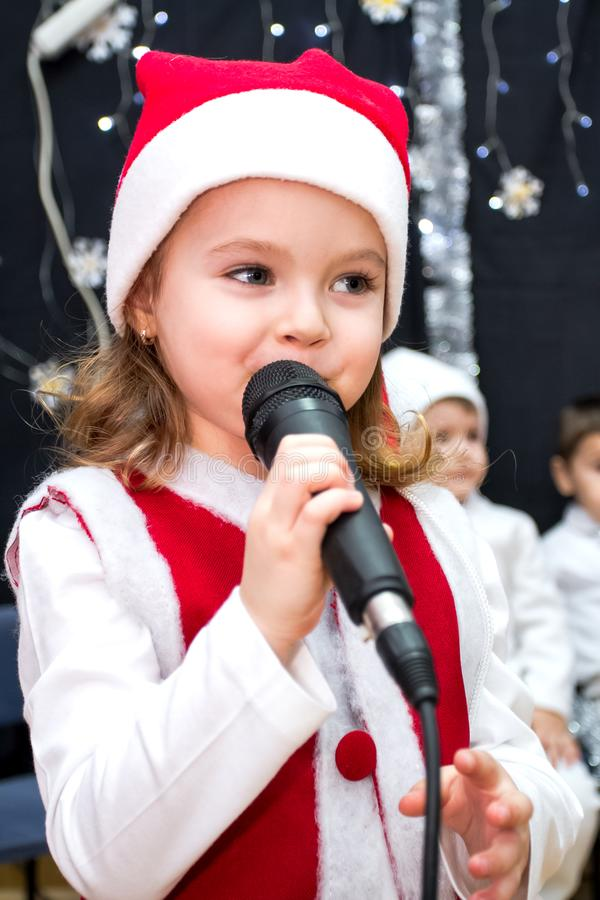 Cute girl in red santa dress holding microphone on stage royalty free stock photos