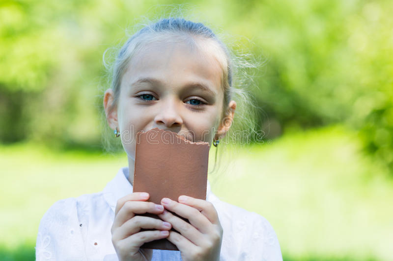 Cute girl with relish eating a chocolate. Girll with relish eating a chocolate outdoore stock photo