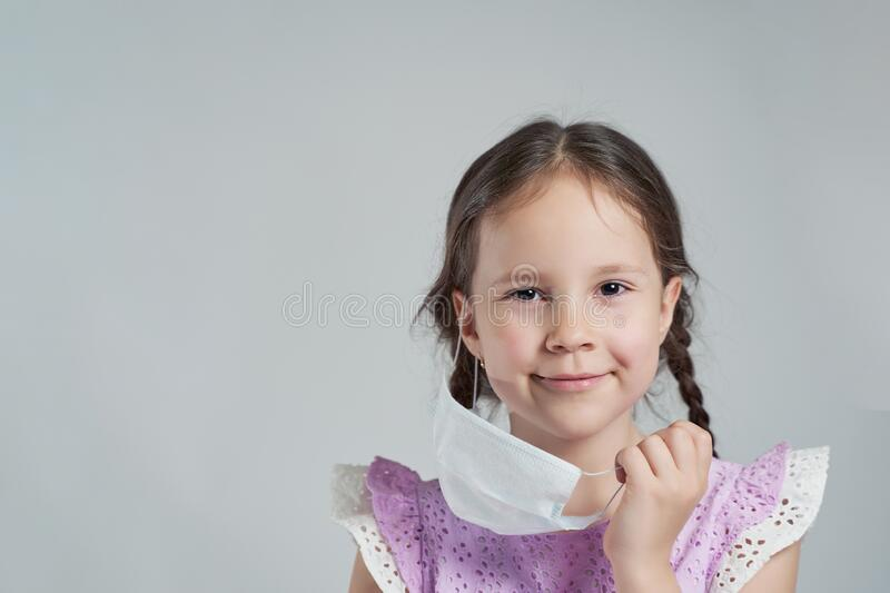 The cute girl removes his mask. there will be an epidemic. we will defeat the coronovirus.  royalty free stock photo