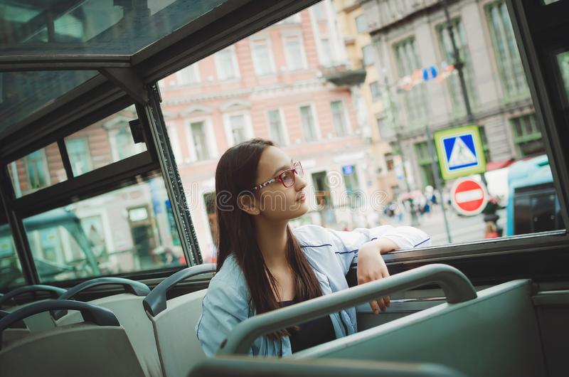 Cute girl rides in a tourist sightseeing bus. royalty free stock photo