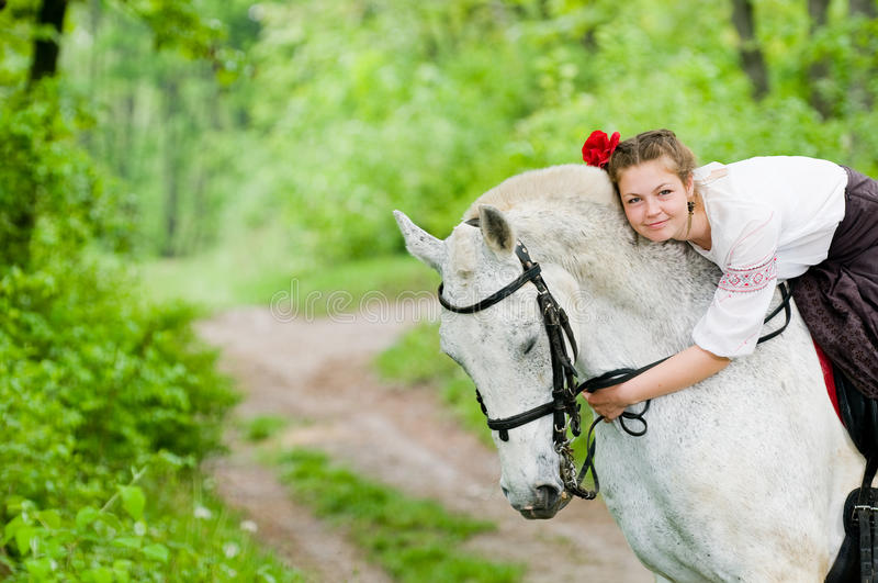Cute girl riding horse. In the forest royalty free stock photo
