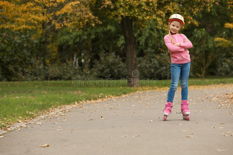 Cute girl roller skating in autumn park. stock images