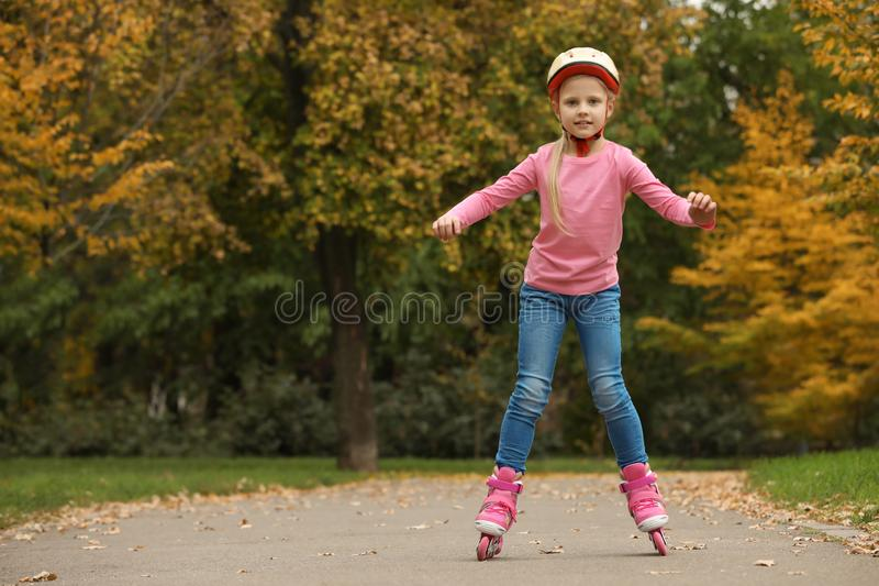 Cute girl roller skating in autumn park royalty free stock photo