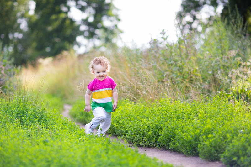 Cute girl running in a beautiful summer field. Cute little girl running in a beautiful summer field on sunny day stock photos