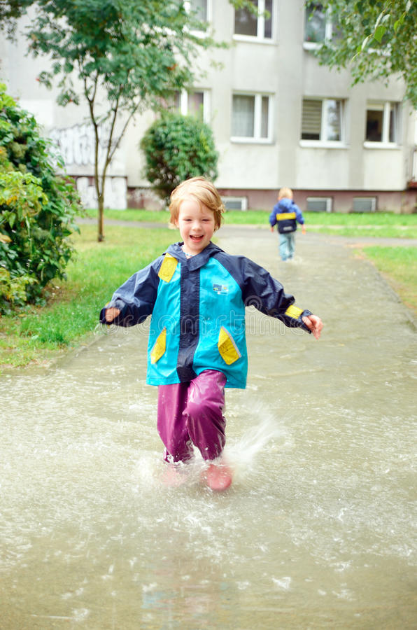 Cute girl running through puddle after the rain. Cute, blonde girl in special clothes running through puddle after the rain royalty free stock photos