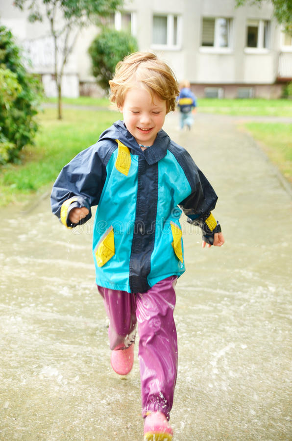 Cute girl running through puddle after the rain. Cute, blonde girl in special clothes running through puddle after the rain royalty free stock photography