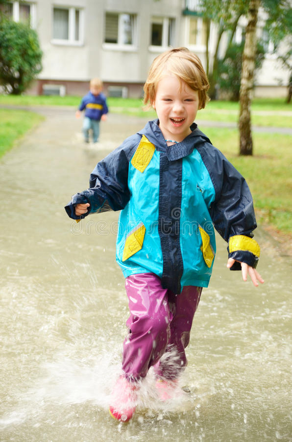 Cute girl running through puddle after the rain. Cute, blonde girl in special clothes running through puddle after the rain stock image