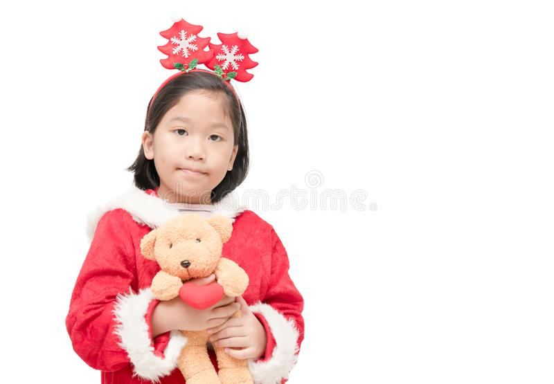Cute girl in santa claus suit with teddy bear doll royalty free stock image