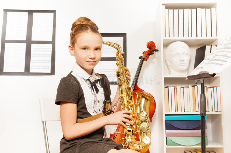 Cute girl in school uniform dress holds saxophone. Cute girl in school uniform dress holding alto saxophone to play in musical school royalty free stock photo