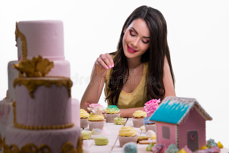 Cute girl seasons the confection. With intention to make it more tasty. High concentration of cream and sugar. Close-up portrait with sweet still-life royalty free stock image