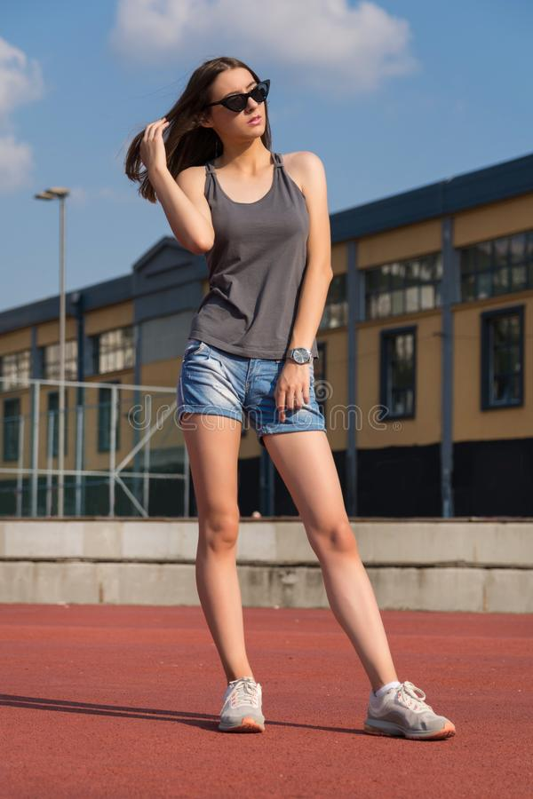 Cute girl in shorts with long legs and summer clothes posing on the playground stock photos