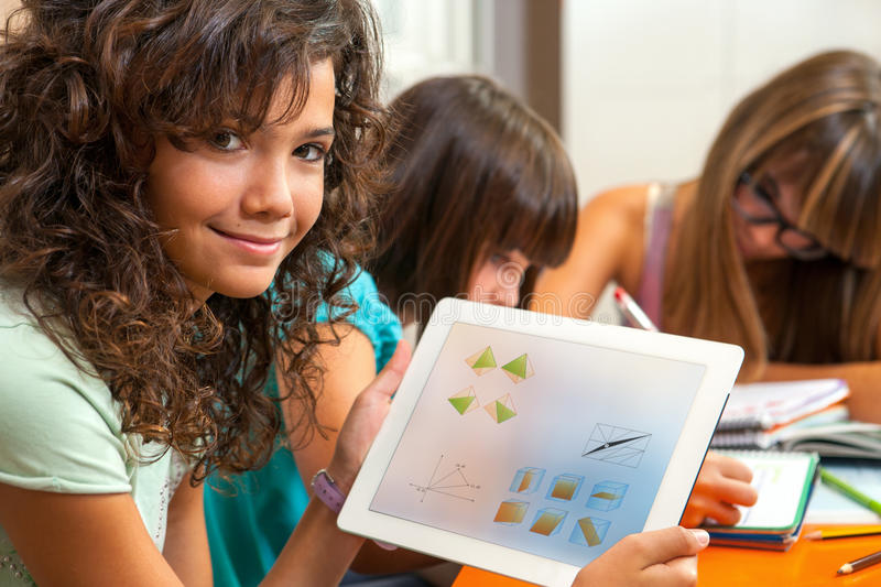Cute girl showing homework on tablet. royalty free stock photography