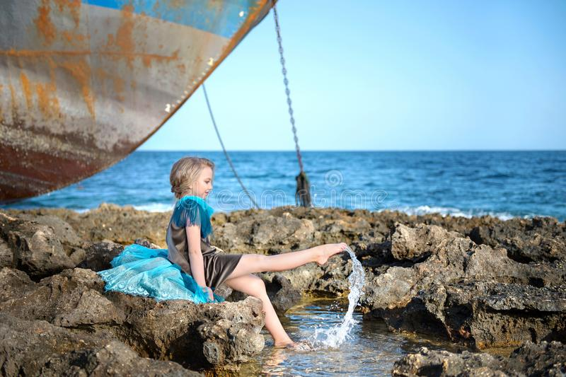 Cute girl sits on a rocky seashore and joyfully splashes with her feet in the water against the background of an abandoned old shi royalty free stock images