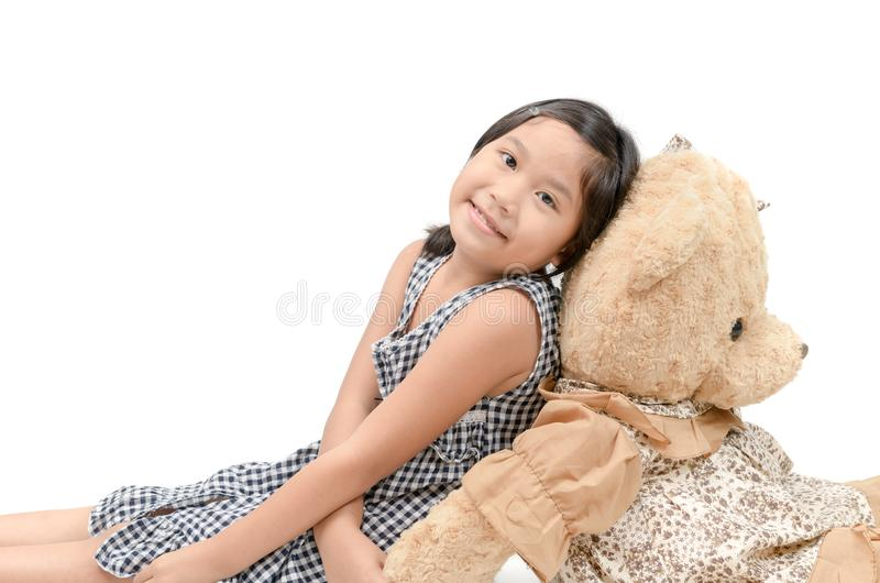 Cute girl sitting with big teddy bear isolated stock images